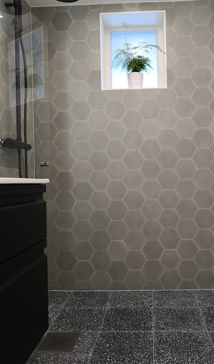 På vegg: Heksagon sementfliser Grey 15x1 cm. På gulv: Sorte terrazzofliser 30x30x1,8 cm